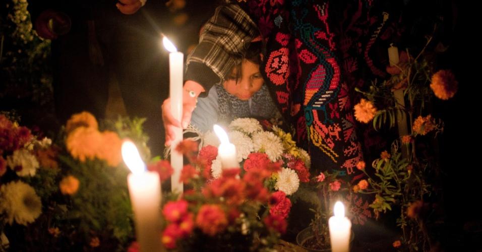 2.nov.2012 - Mulher acende vela para parente morto no cemitério de San Gregório Atlapulco, na cidade do México