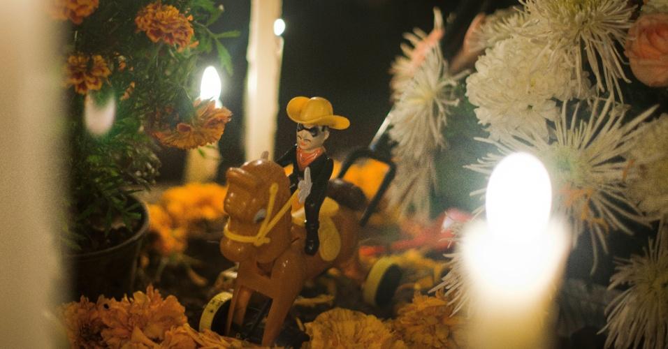 2.nov.2012 - Túmulo de criança no cemitério de San Gregório Atlapulco, na cidade do México, é enfeitado com doces e brinquedos