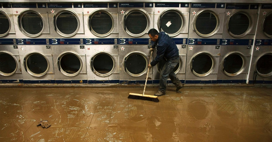 2.nov.2012 - Eddie Liu usa vassoura para retirar lama e água de enchente de lavanderia quatro dias após passagem do furacão Sandy pelos Estados Unidos, no bairro de Coney Island, em Nova York