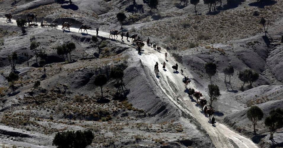 3.nov.2012 - Afegãos caminham com camelos por estrada do leste do país, próximo da fronteira com o Paquistão
