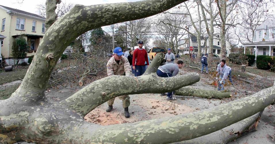 3.nov.2012 - Morador de Nova Jersey usa uma motosserra para cortar uma árvore caída após a passagem da tempestade Sandy
