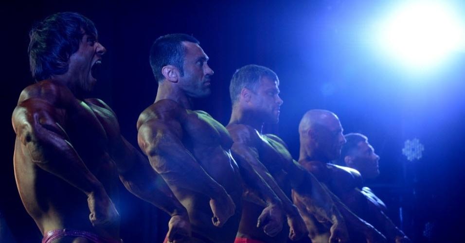 Competidor grita enquanto flexiona os músculos e exibe sua forma em campeonato de fisiculturismo