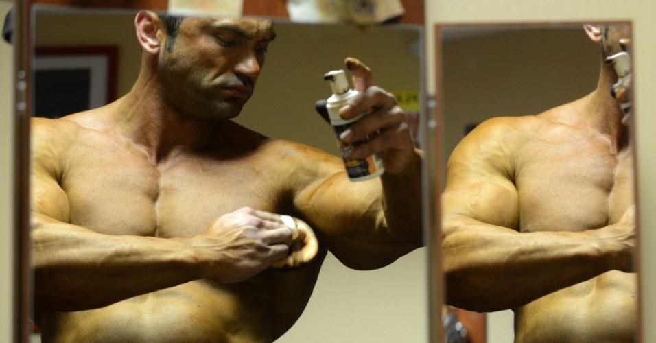 Competidor se prepara e passa óleo no corpo para disputar campeoanto de fisiculturismo na Rússia
