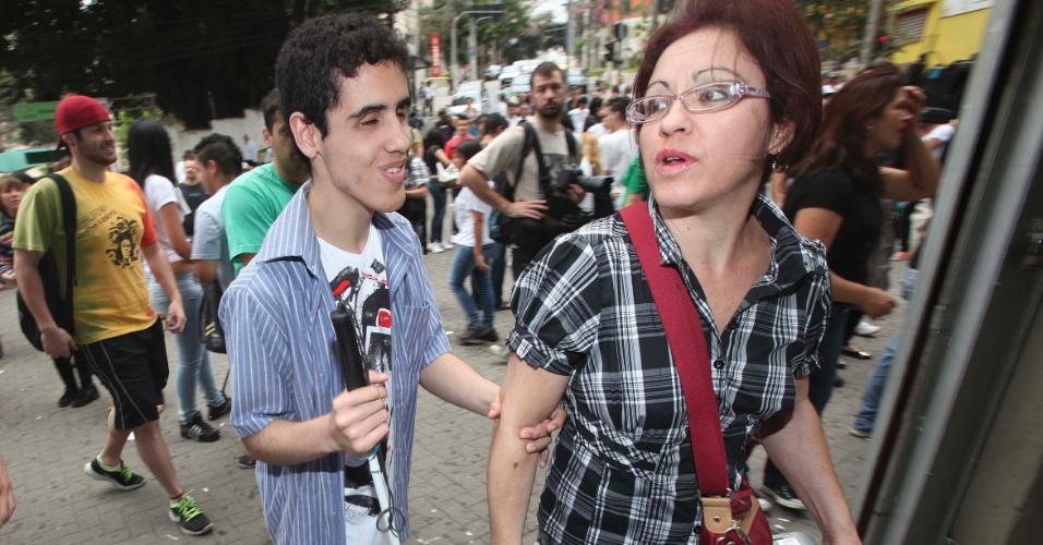 3.nov.2012 - Mãe leva filho deficiente visual para prova do Enem 2012