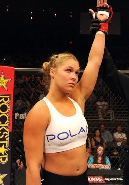 Ronda Rousey tem o braço erguido após combate, em mais uma vitória