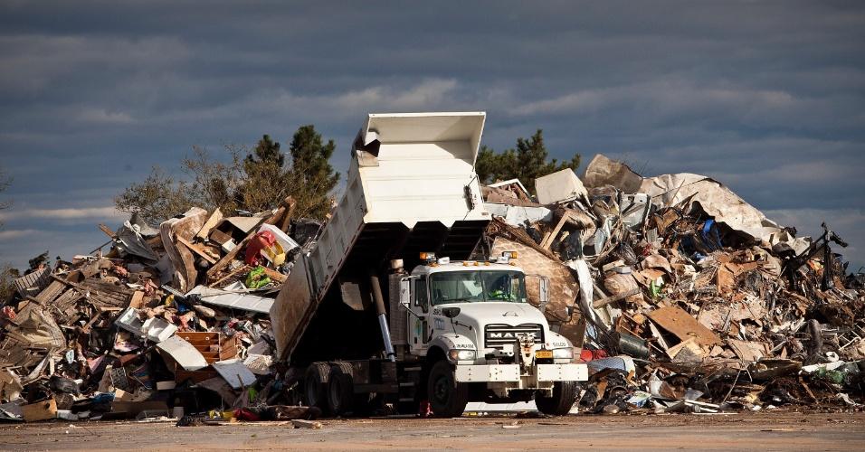 Um caminhão despeja lixo coletado em casas depois da passagem da super tempestade Sandy em Nova York