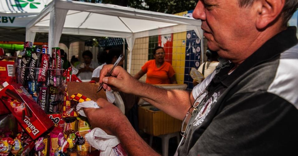 4.nov.2012 - Ambulante testa caneta que vende para candidatos ao segundo dia de provas do Enem 2012 em Pernambuco