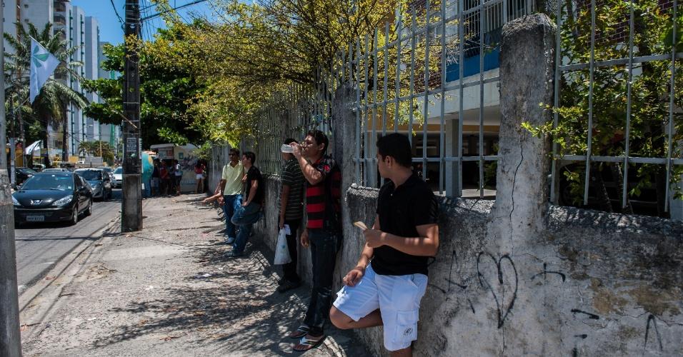 4.nov.2012 - Candidatos se escondem do sol antes de terem acesso aos locais de prova do segundo dia do Enem 2012 em Pernambuco