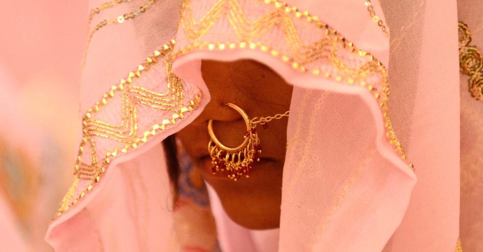 4.nov.2012 - Noiva muçulmana aguarda o começo da missa de casamento celebrada para 47 casais em Ahmedabad, Índia