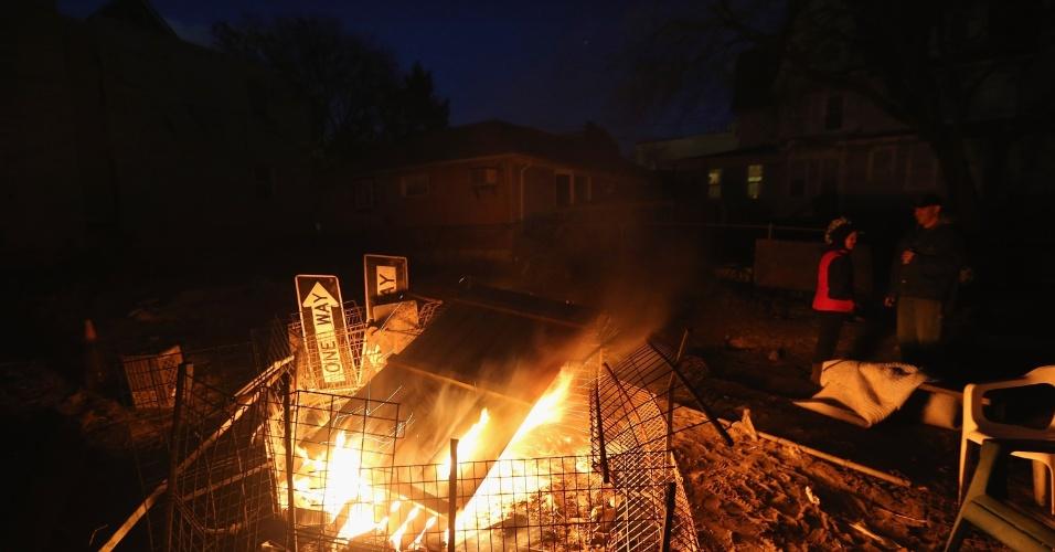4.nov.2012 - O casal Ellen Saunter e Mike Quinn improvisam fogueira do lado de fora de residência com destroços da tempestade Sandy