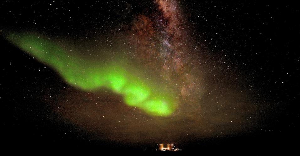 5.nov.2012 - Aurora Austral mancha de verde o céu do Pólo Sul logo acima da estação de pesquisa Concordia. Ao seu redor, uma névoa de luz vermelha representa a Via Láctea - a faixa brilhante é uma visão da parte mais central e estrelada da galáxia, já que a Terra fica dentro de uma região mais periférica. A imagem foi divulgada nesta segunda-feira (5) pela  Agência Espacial Europeia (ESA, na sigla em inglês)