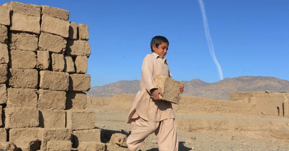 Jovem afegão carrega tijolo em uma fábrica nos arredores de Herat, no Afeganistão, nesta segunda-feira (5)