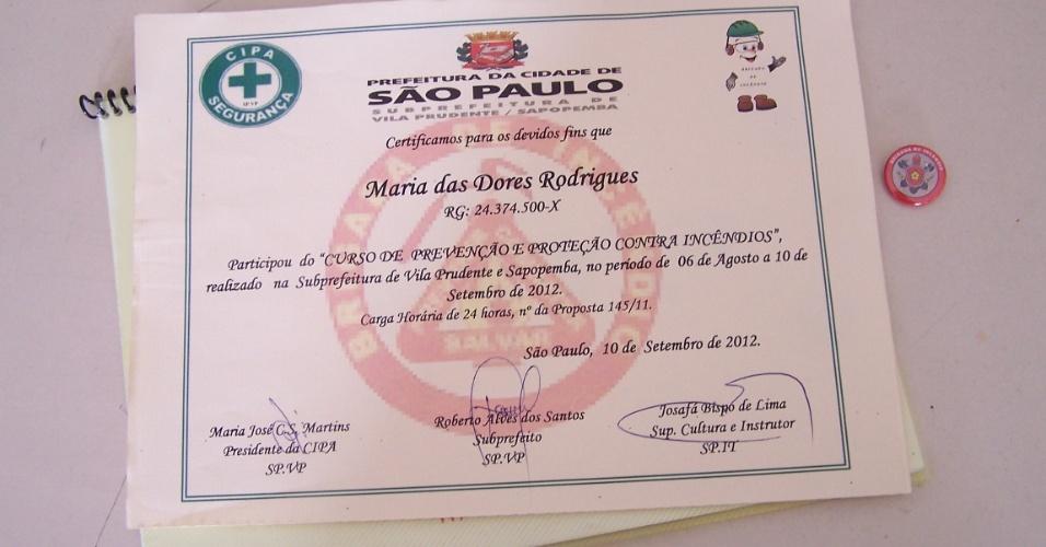 5.nov.2012 - Maria das Dores Rodrigues, moradora da favela de Vila Prudente, na zona leste de São Paulo, recebeu um diploma após participar do curso de brigada de incêndio oferecido pela prefeitura. Ao lado, o crachá que os brigadistas recebem e que servem como identificação