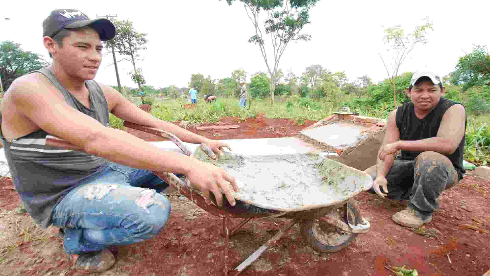 Os índios reclamam da falta de estrutura dos cemitérios das aldeias. Tiago Ávila e Adeilson Machado organizam o túmulo onde a avó foi sepultada - Ademir Almeida/UOL