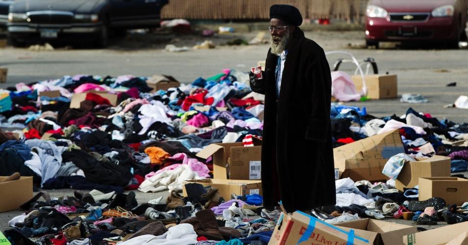 6.nov.2012 - Homem caminha em meio a roupas doadas para as vítimas do furacão Sandy, no bairro de Queens, em Nova York. As doações estão empilhadas em um estacionamento