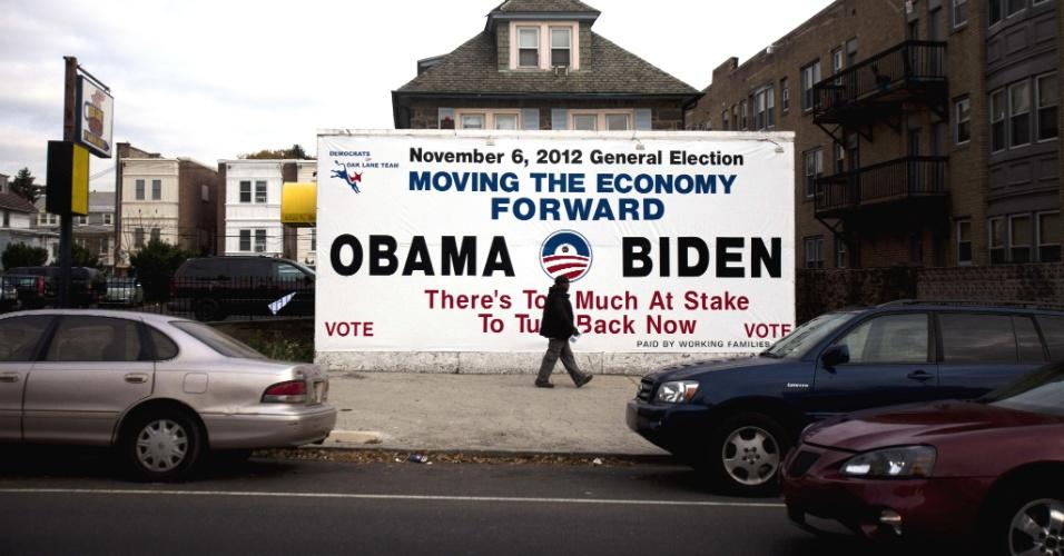 6.nov.2012 - Homem passa diante de painel de campanha apoiando o presidente norte-americano, Barack Obama, e seu vice, Joe Biden, em Filadélfia, Pensilvânia