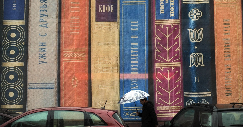 6.nov.2012 - Homem passa por uma cobertura de andaimes que retrata livros no centro de Moscou, na Rússia