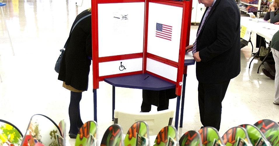 6.nov.2012 - Moradores de Dubuque, Iowa, votam em urnas localizadas em uma loja de departamento, ao lado de estante de pranchas de snowboard. Iowa é um dos Estados-chave, onde as eleições de 2012 podem ser decididas