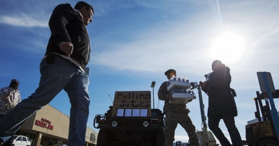 6.nov.2012 - Soldado da Guarda Nacional norte-americana auxilia eleitor a carregar caixa com garrafas de água, perto de local de votação, no distrito de Queens, em Nova York, durante as eleições presidenciais dos EUA