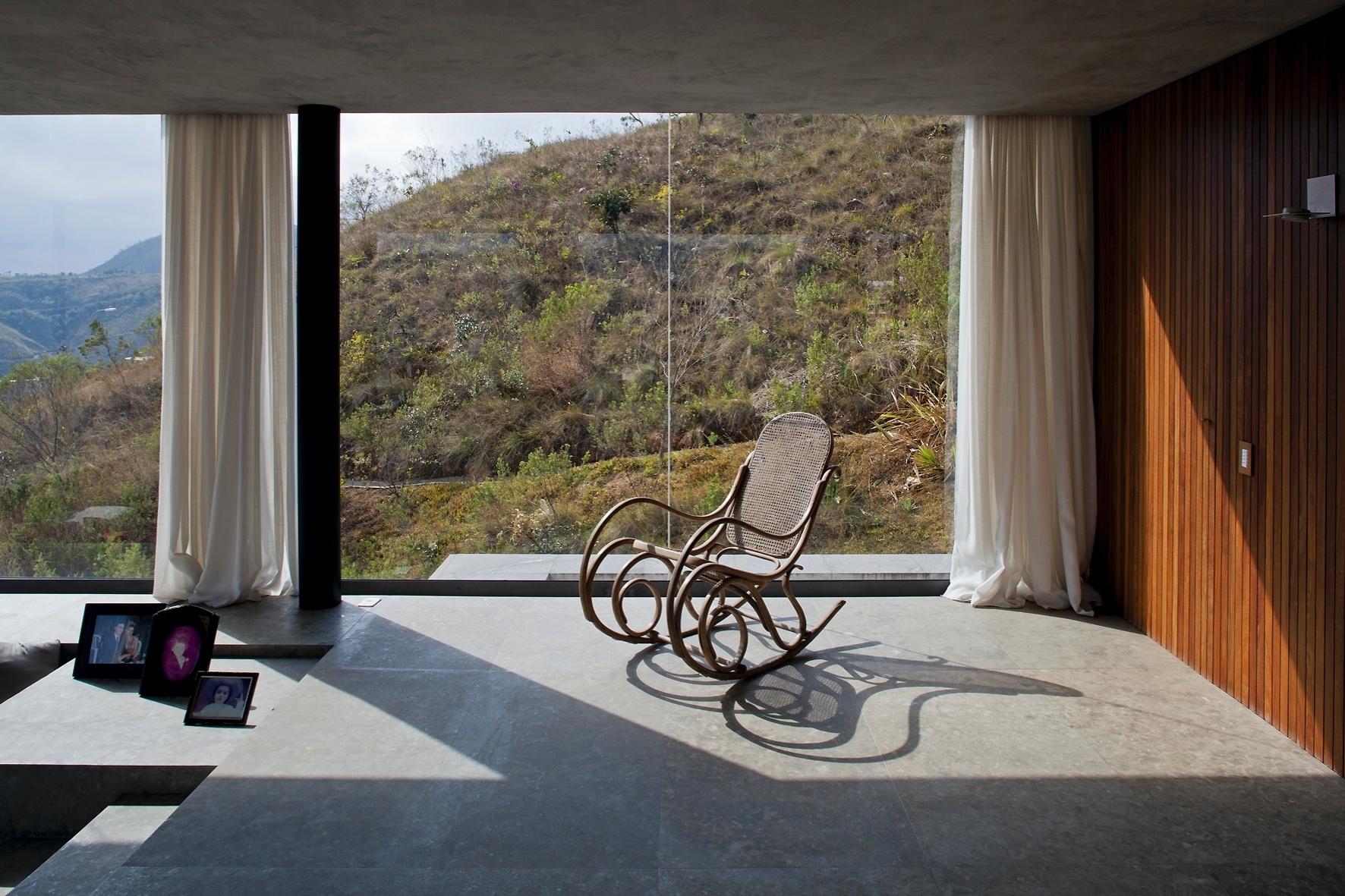 Grandes panos de vidro proporcionam belas vistas e boa entrada de luz aos ambientes sociais da casa EG, assinada pelo arquiteto Marcelo Alvarenga, em Nova Lima (MG). A privacidade dos moradores é garantida pelas cortinas de linho natural