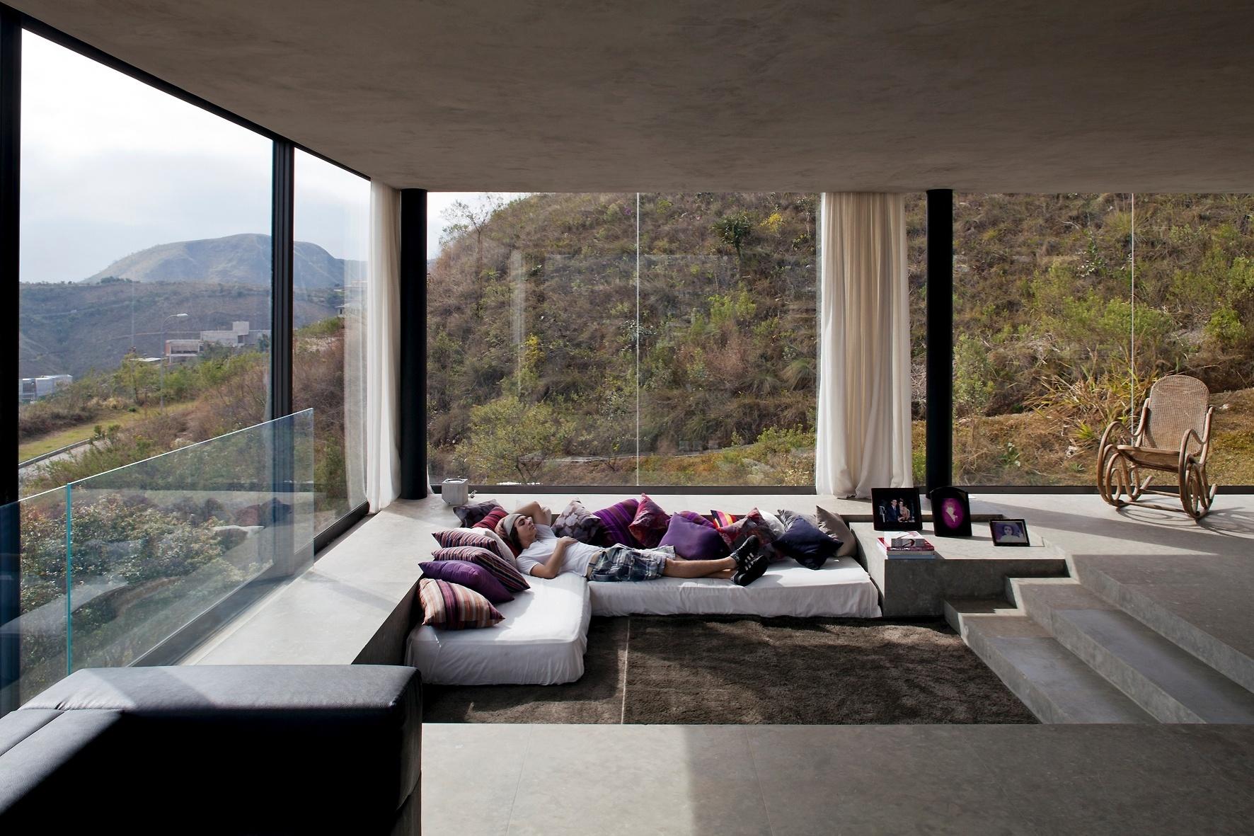 Implantado no rebaixo do chão, um sofá bom de deitar aconchega os moradores e visitantes no volume que abriga a área social da casa EG, projetada por Marcelo Alvarenga, em Nova Lima (MG)