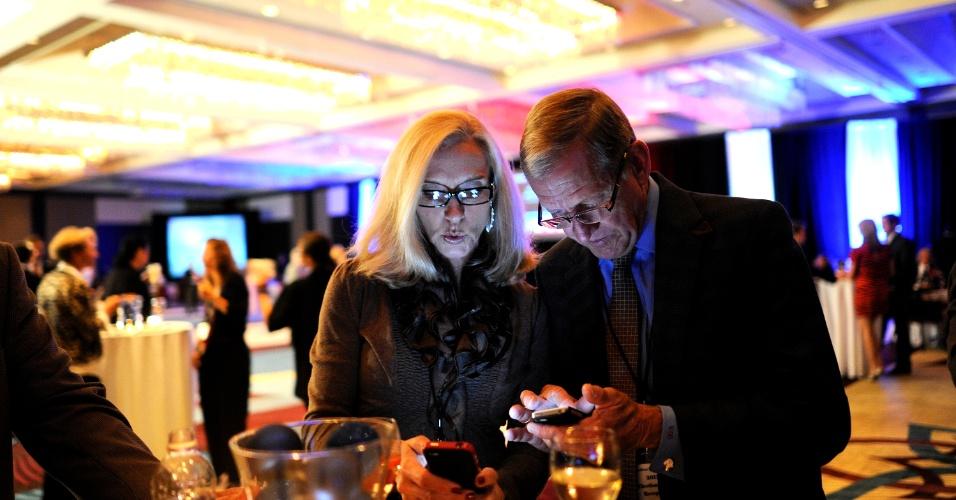 7.nov.2012 - Apoiadores de Mitt Romney, candidato republicano à presidência dos EUA, checam seus smartphones por resultados das votações, durante recepção da noite das eleições patrocinada pelo partido Republicano em Tampa, Flórida