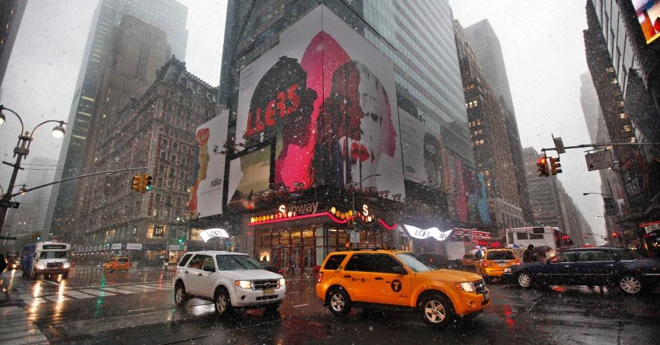 7.nov.2012 - Carros passam na Times Square, em Nova York (EUA), durante tempestade de inverno fez cair neve na cidade e ameaça trazer ventos perigosos e inundações, uma semana após a passagem do furacão Sandy
