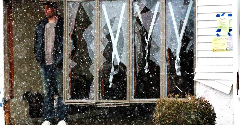 7.nov.2012 - Chris Brady observa, ao lado de janelas que, apesar do reforço, não suportaram os ventos do furacão Sandy, a neve caindo na cidade de Lindenhurst, Nova York. O prefeito de Nova York, Michael Bloomberg, calcula entre 30 e 40 mil o número de desabrigados na cidade