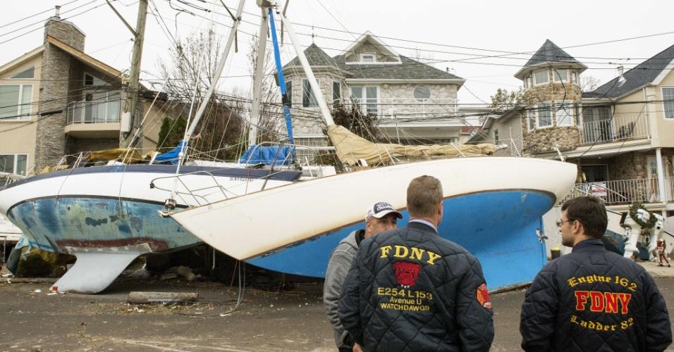 7.nov.2012 - Homens observam barcos arrastados até a costa de Great Kills, em Nova York, durante passagem do furacão Sandy