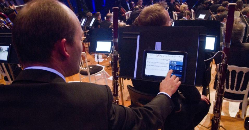 7.nov.2012 - Músico da Orquestra Filarmônica de Bruxelas usa tablet durante execução de obra na capital da Bélgica. A mudança das partituras de papel para o meio digital faz parte de um projeto do grupo de músicos. Para a iniciativa, a fabricante sul-coreana Samsung forneceu os tablets