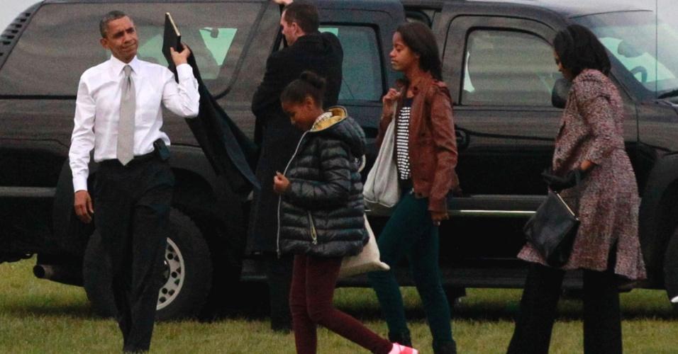 7.nov.2012 - O presidente reeleito norte-americano, Barack Obama, a primeira-dama, Michelle Obama, e as filhas do casal, Malia e Sasha se encaminham ao avião presidencial, o