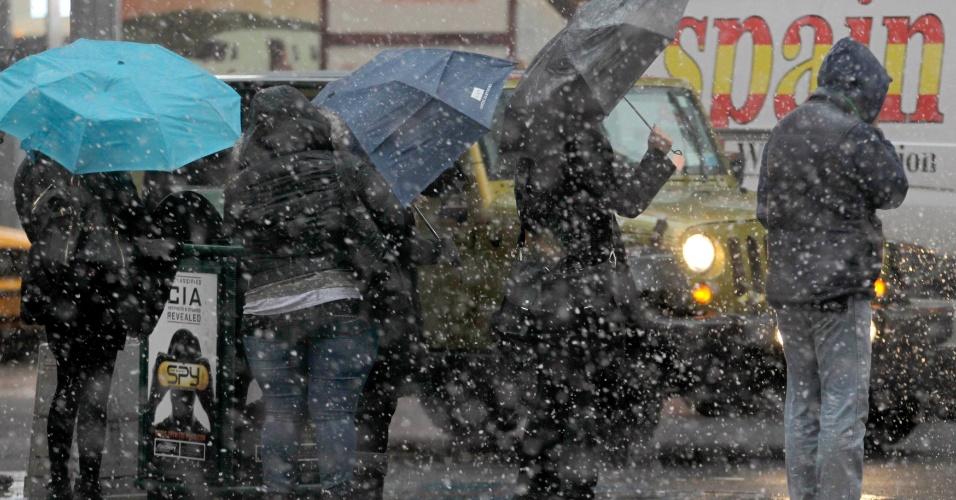 7.nov.2012 - Pessoas se agasalham enquanto esperam ônibus, em Nova York (EUA). Uma tempestade de inverno fez cair neve na cidade e ameaça trazer ventos perigosos e inundações, uma semana após a passagem do furacão Sandy