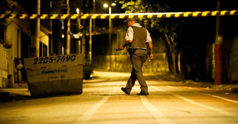 7.nov.2012 - Policial caminha pela rua Tomaso Ferrara, em Itaquera, zona leste de São Paulo, onde dois homens foram mortos a tiros na noite de terça-feira (6)