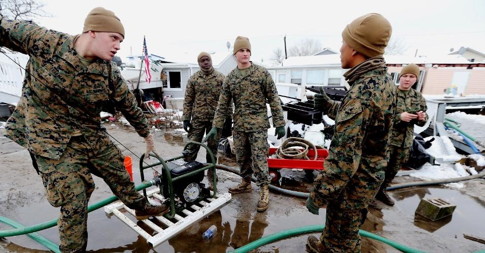 8.nov.2012 - Fuzileiros navais norte-americanos tentam ligar motor para bombear água de área inundada após a passagem de uma tempestade fria de nordeste que trouxe mais transtornos ao bairro de Breezy Point, em Nova York, que havia sido um dos mais arrasados pelo furacão Sandy