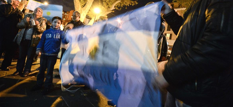 8.nov.2012 - Garoto ajuda a estender uma bandeira argentina durante protesto contra o governo de Cristina Kirchner e problemas como a crescente inflação - Andreas Solaro/AFP