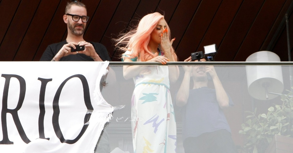 """Após sair na sacada do hotel com a camisa da seleção brasileira de futebol, Lady Gaga retorna usando um vestido branco. Ao lado da bandeira """"I Love Rio"""", ela acena e manda beijos para os fãs cariocas (8/11/12)"""