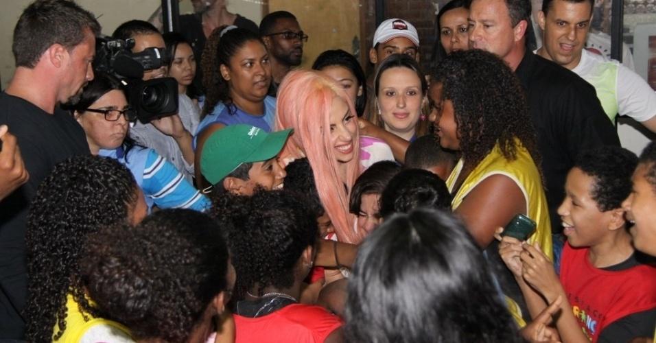 """Ao chegar no espaço Criança Esperança no Morro do Cantagalo, no Rio de Janeiro, Lady Gaga é abraçada pelas crianças da comunidade. """"Nunca vou esquecer o Rio. Vocês fizeram meu coração ficar em chamas"""", escreveu a cantora em seu Twitter depois da visita (8/11/12)"""