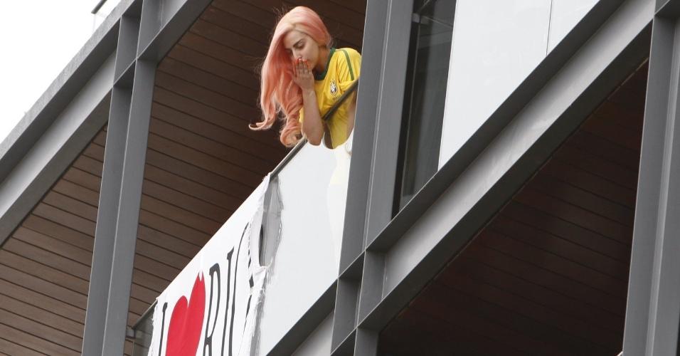 Vestida com a camisa da seleção brasileira, Lady Gaga manda beijos para os fãs cariocas da sacada do hotel Fasano, no Rio de Janeiro (8/11/12)