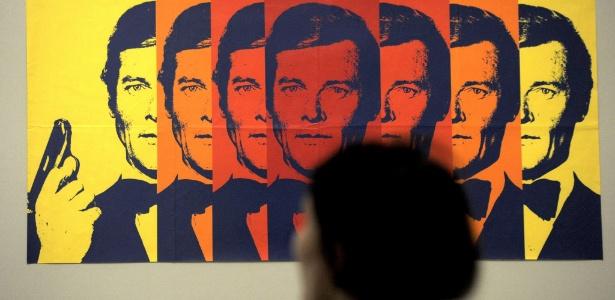 """Visitante observa pôster da exposição """"50 anos de James Bond"""", na Alemanha em 2003"""