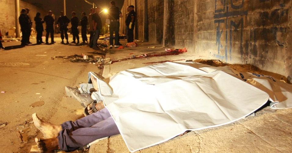 """9.nov.2012 - Corpos de três vítimas de uma chacina ficam estirados na rua Fernando de Noronha, na Vila Sacadura Cabral, na periferia de Santo André (SP), local também conhecido como a """"cracolândia"""" da cidade"""