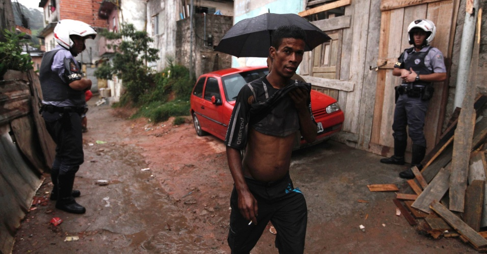 9.nov.2012 - Morador passa por policiais durante uma operação saturação realizada em favela do bairro da Brasilândia, na zona norte de São Paulo, palco de uma série de ataques a policiais, ônibus e pessoas em geral