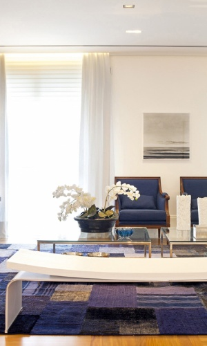 No living do apartamento no bairro Cambuí, em Campinas (SP), a arquiteta Elaine Carvalho usa o tom azul marinho para dar um ar masculino à decoração de base branca. Ao fundo, as duas poltronas clássicas foram revestidas em linho e, sobre o tapete retalhado da By Kamy, está em destaque, o banco Érea de linhas modernas