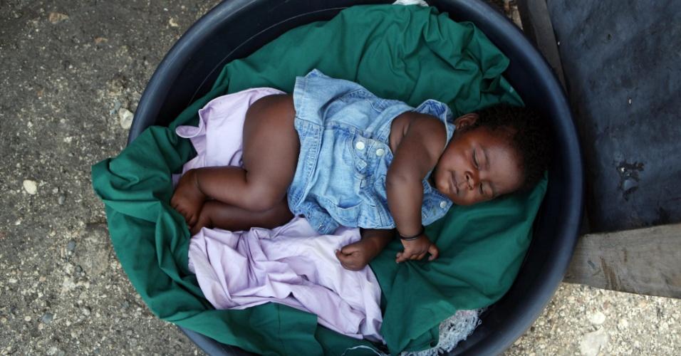 10.nov.2012 - Criança dorme em bacia de plástico na entrada de um campo de refugiados na cidade de Porto Príncipe, no Haiti. O país caribenho foi atingido no mês passado pelo furacão Sandy