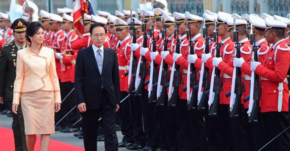 10.nov.2012 - O primeiro-ministro da Tailândia, Yingluck Shinawatra (à esquerda) e o presidente sul-coreano, Lee Myung-bak, revistam as tropas durante cerimônia de boas-vindas na Casa do governo em Bancoc (Tailândia)