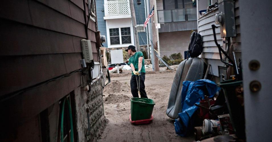 10.nov.2012 - O voluntário Phil Amabile carrega balde de areia durante processo de limpeza de danos causados pelo furacão Sandy. Neste sábado, Michael Bloomberg, prefeito de Nova York, anunciou que o dia seria dedicado ao trabalho voluntário para limpeza das ruas da cidade