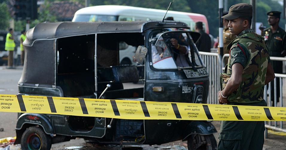Soldados montam guarda próximo a táxi que teria sido usado por presidiários em fuga após motim na prisão de Welikada, em Colombo, no Sri Lanka