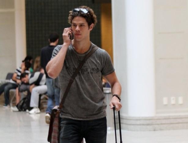 """Com cabelos mais longos, o ator José Loreto, que interpretou Darkson em """"Avenida Brasil"""", se prepara para embarcar no aeroporto Santos Dumont, no Rio de Janeiro (13/11/12)"""