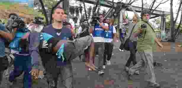 Funcionário da Assistência Social carrega uma suposta dependente de crack durante operação de combate à droga - Fabio Teixeira/AE