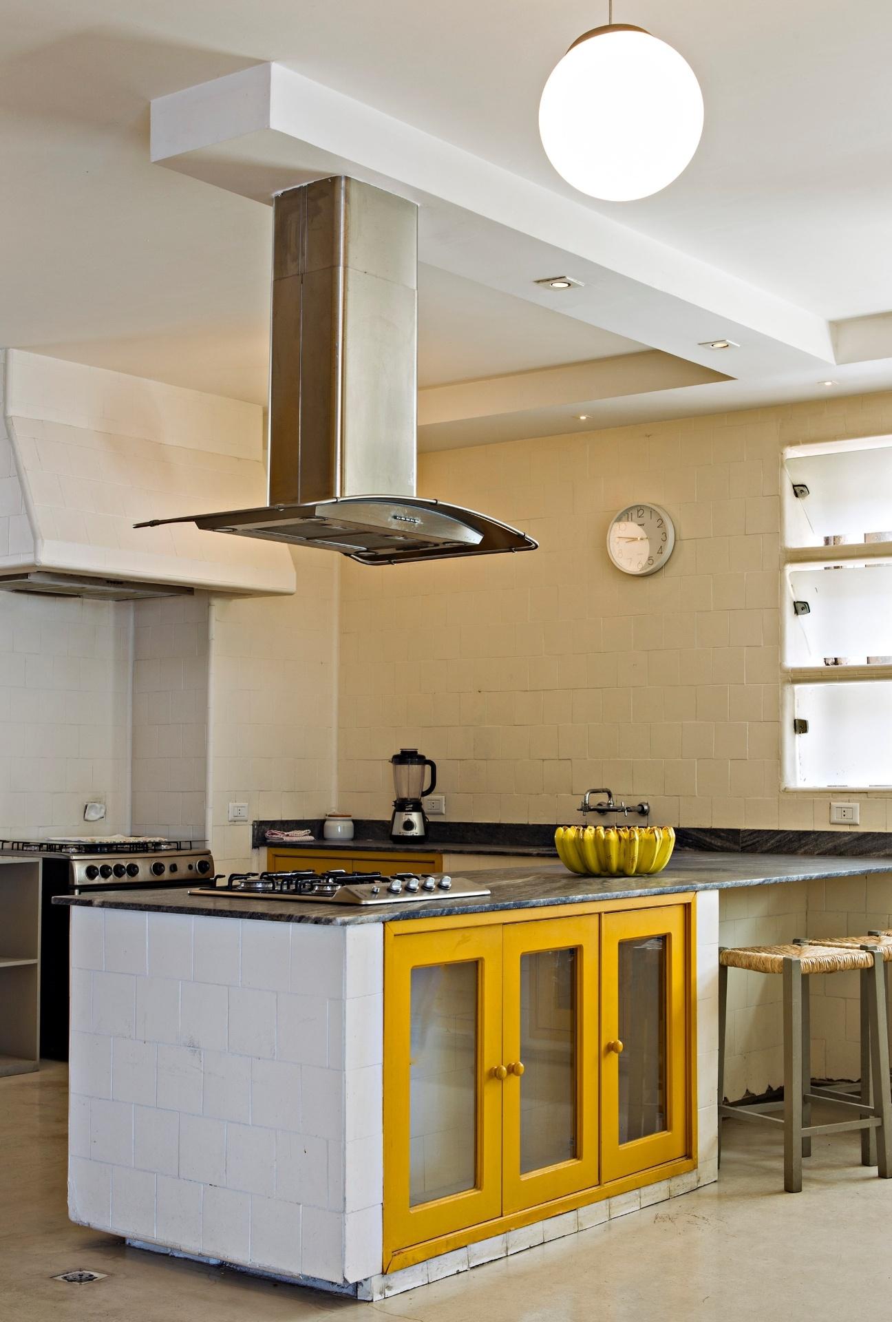 Como os proprietários queriam uma cozinha inspirada nas italianas antigas, os arquitetos instalaram uma ilha com cooktop e armários com portas de vidro e azulejos garimpados. Tudo combinando com bancos de palha que dão o ar