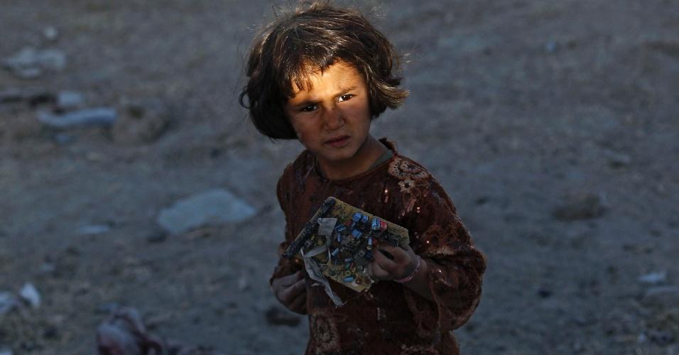 Criança recolhe material reciclável em lixão de Cabul, no Afeganistão